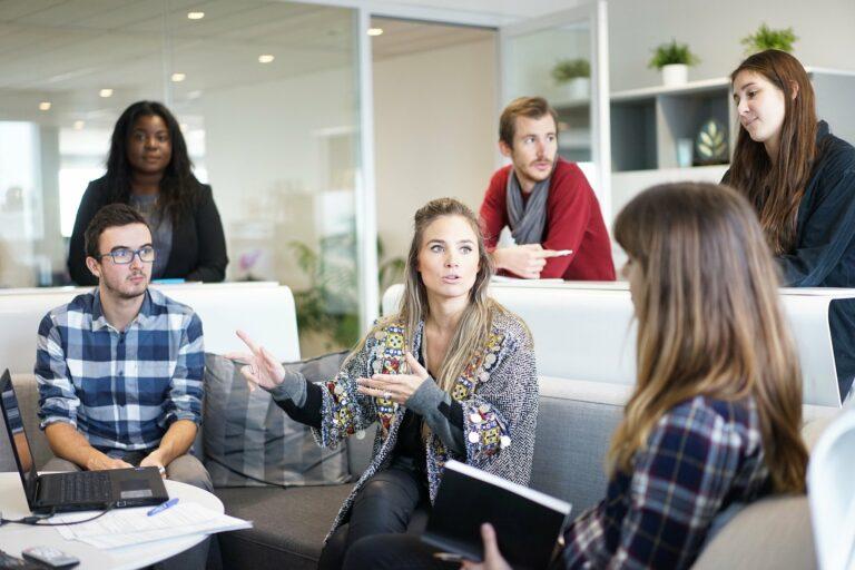 foto de várias pessoas reunidas em um sofá e em volta de uma mesa. ao fundo vemos uma parede de vidros, plantas e um escritório. imagem ilustrativa para texto terceirização no franchising.