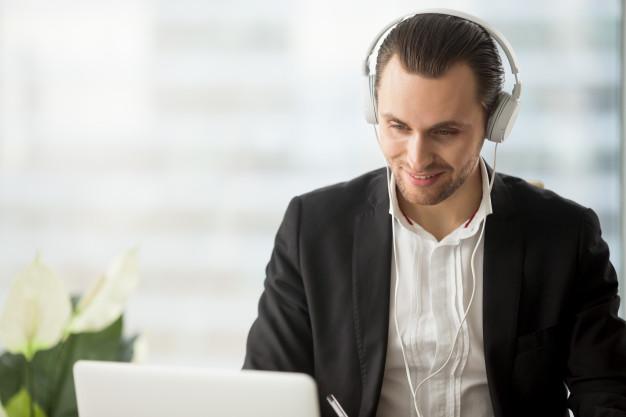 Imagem de um homem olhando para o computador e usando um fone de ouvido.