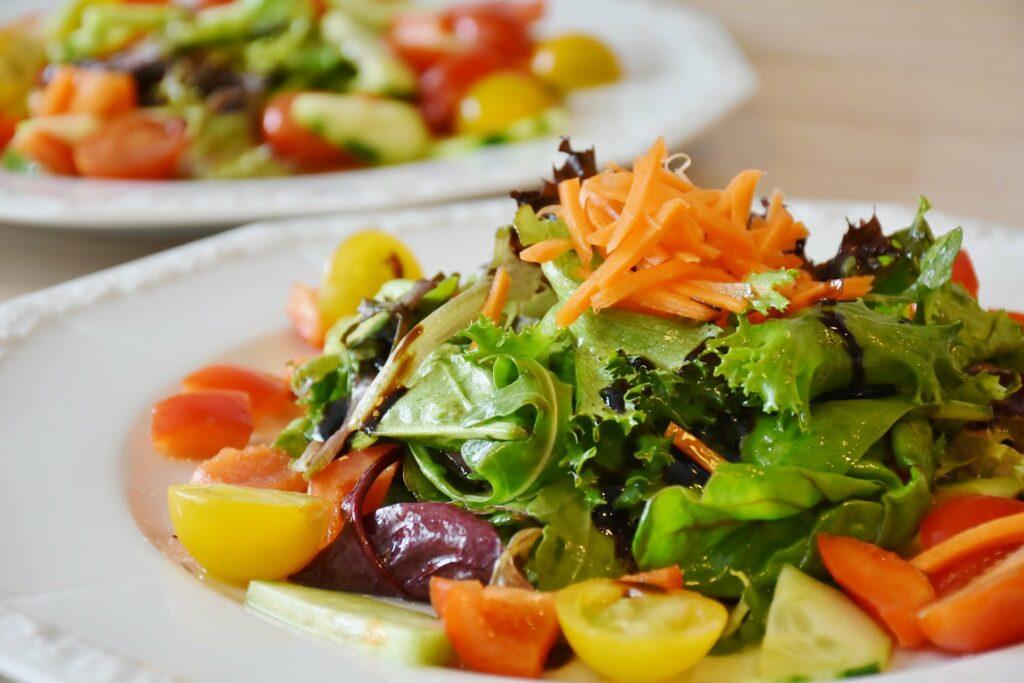 Prato branco com uma salada colorida (imagem ilustrativa). Texto: franquia barata e lucrativa.