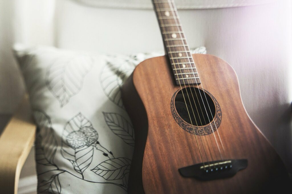 Foto de um violão marrom em uma poltrona brancas (imagem ilustrativa). Imagem ilustrativa texto franquias baratas e lucrativas para cidades pequenas.