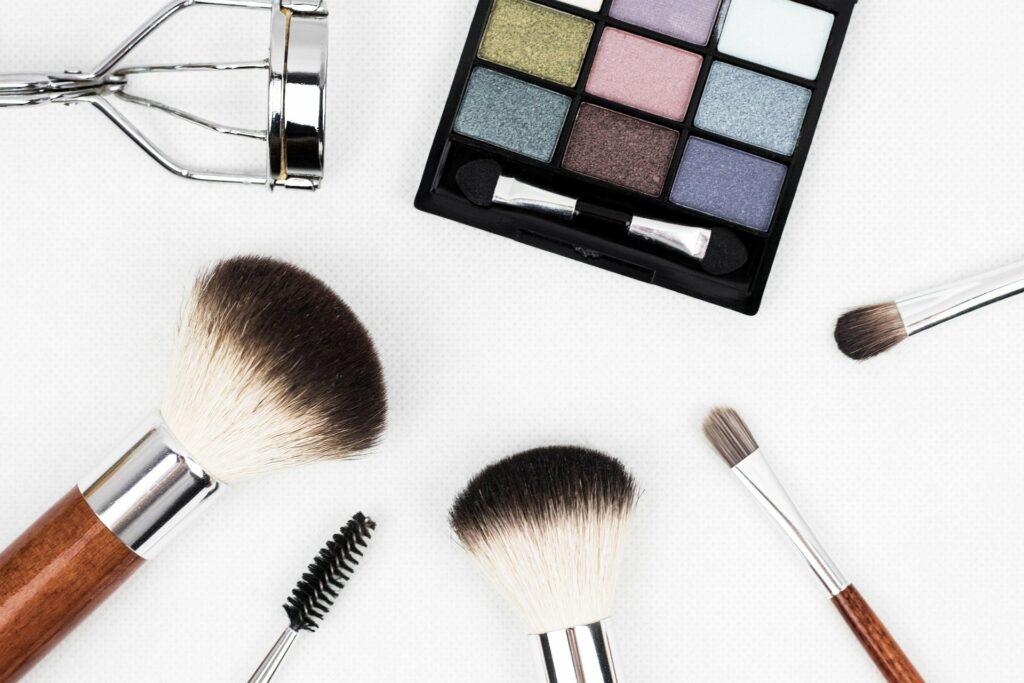 Foto de pinceis e acessórios de maquiagem ao lado de uma paleta de sombras (imagem ilustrativa). Texto: franquias baratas e lucrativas para cidades pequenas.