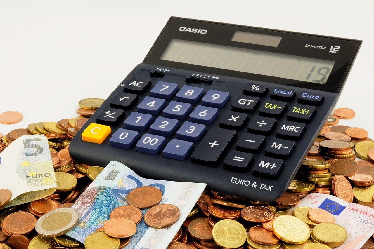 Imagem de uma calculadora em cima de moedas e notas de dinheiro.