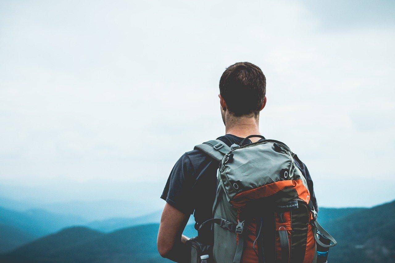 Imagem de um homem de mochila contemplando o horizonte. Imagem ilustrativa texto franquias de 50 mil.